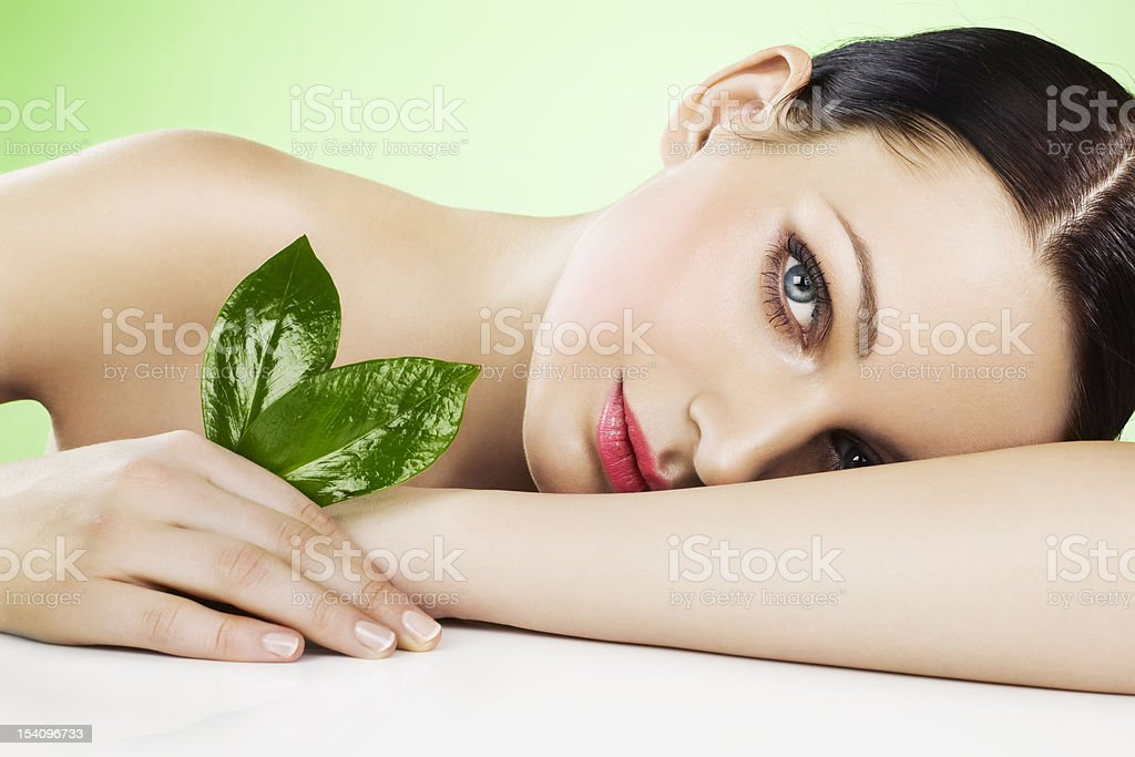 Woman with beautiful complexion holding two leaves stock photo