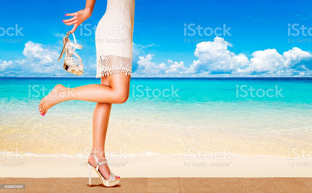 Woman with beautiful heels running in the beach side street. stock photo
