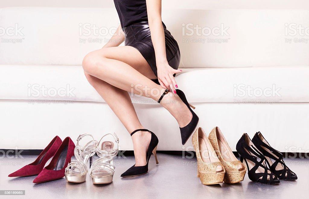 Woman with beautiful legs choosing shoes. stock photo