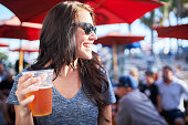 woman with beer at outdoor bar or restaurant patio