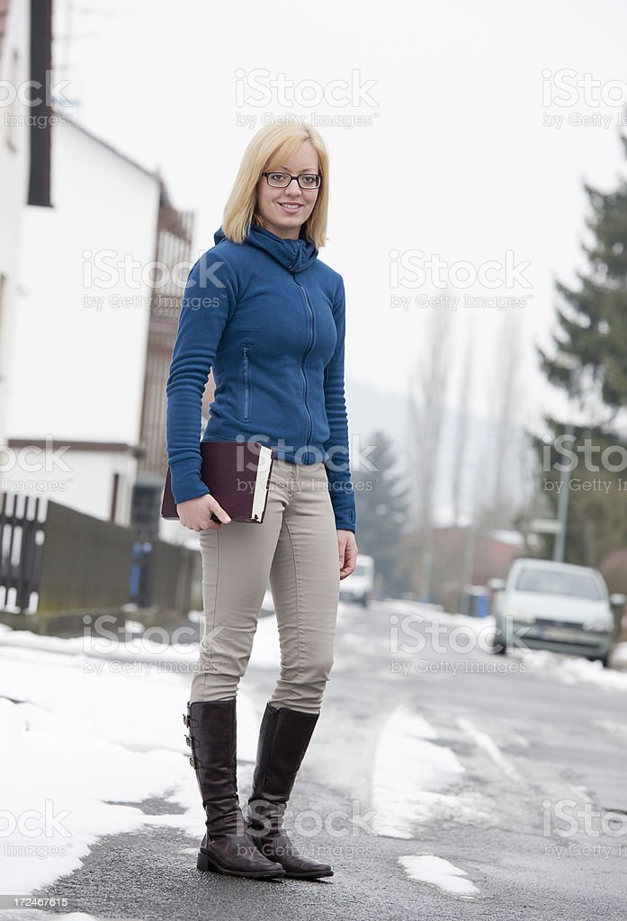 Woman with bible walking over street royalty-free stock photo