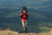 Woman with big backpack in mountains