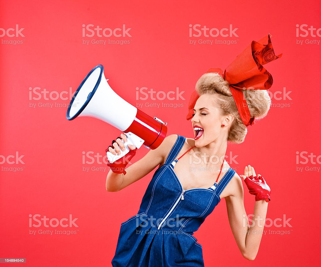 Woman with big hair ribbon shouting into megaphone stock photo