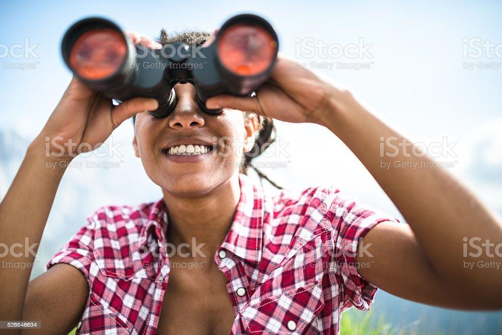 woman with binocular on top of mountain stock photo