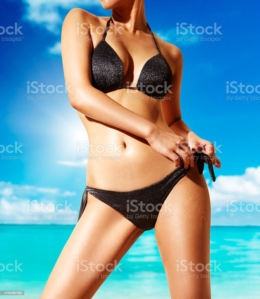 Woman with black bikini on beach. Beautiful body tanned skin. stock photo