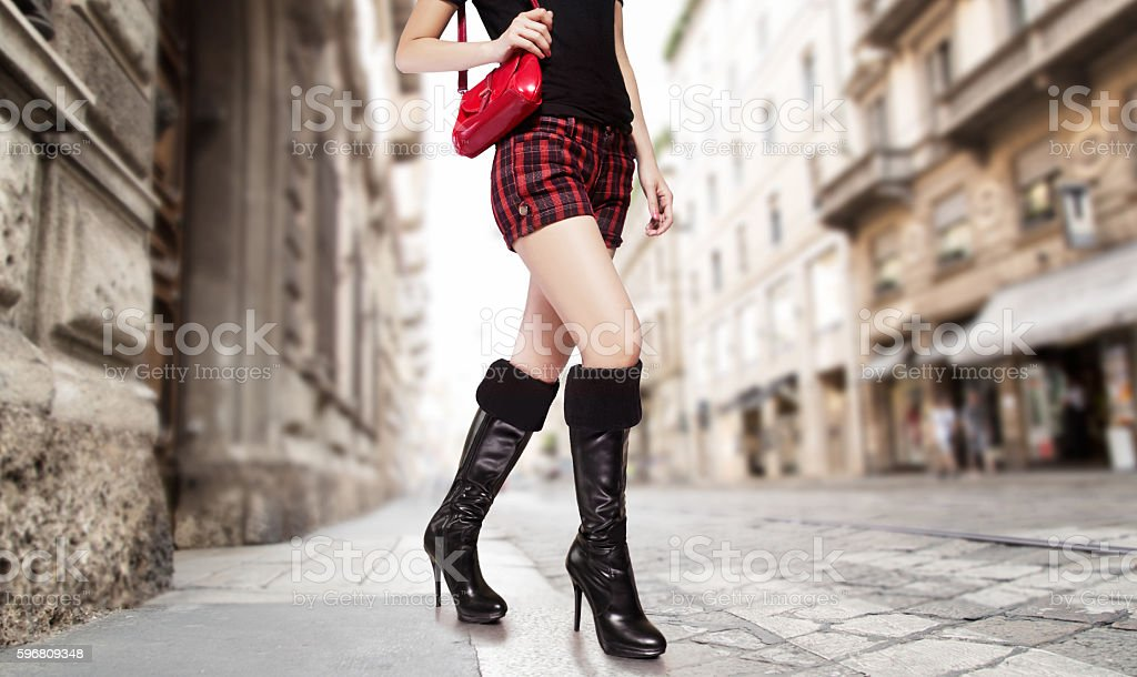 Woman with black boots,handbag purse,shorts in the city. stock photo