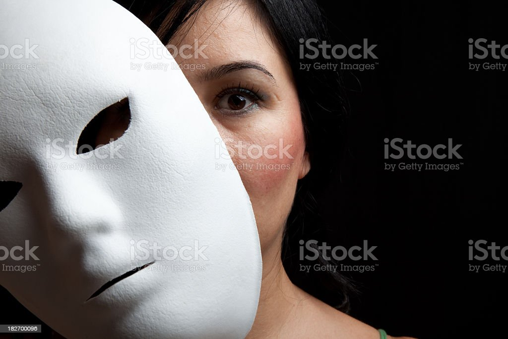 Woman With Black Hair And Dark Eyes Hiding Behind Mask stock photo