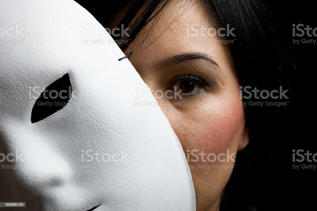 Woman With Black Hair And Eyes Peeking Behind White Mask stock photo