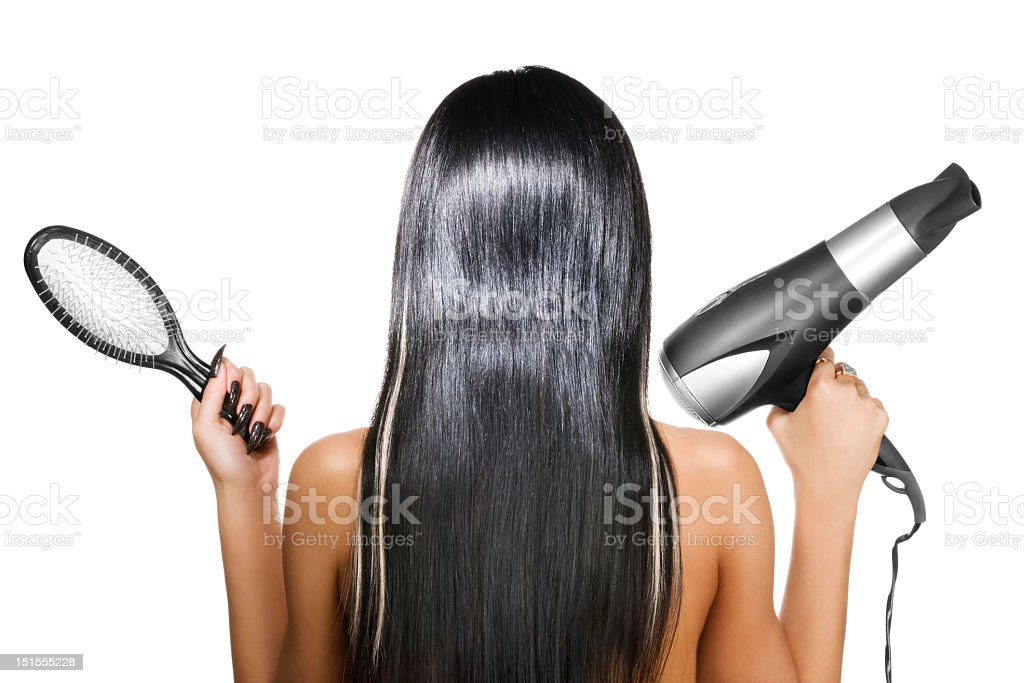 A woman with black hair holding a brush and hairdryer royalty-free stock photo