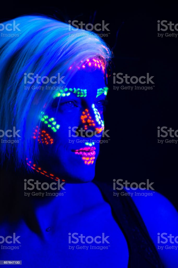 Woman with black light paint on face, profile head and shoulders. stock photo