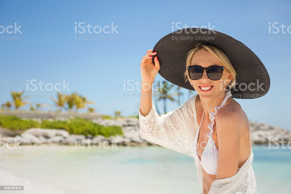 Woman with black summer hat on the beach stock photo