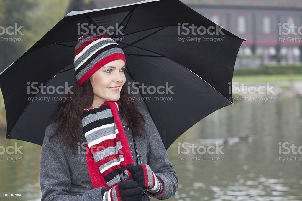 Woman with black umbrella in the park stock photo