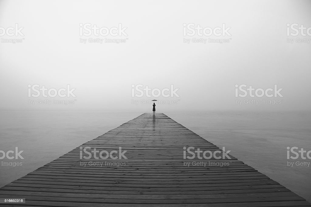 woman with black umbrella looking infinity in a surreal place stock photo