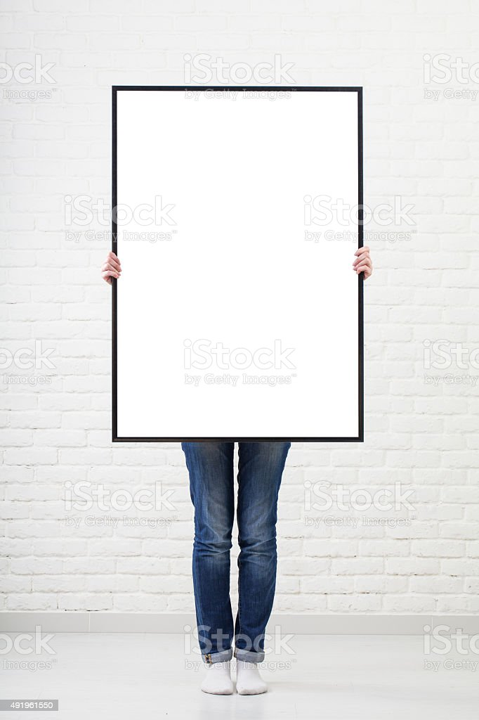 woman with  blank poster on wall background stock photo