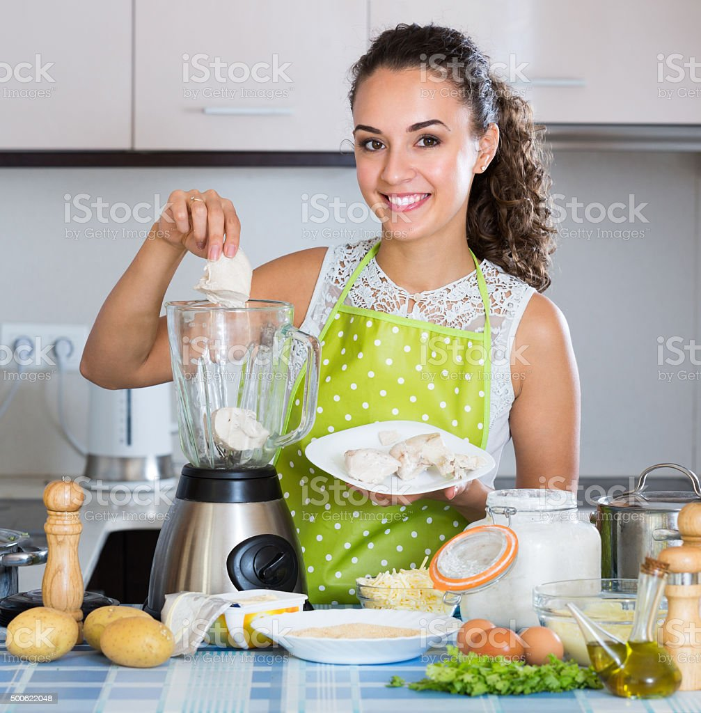 Woman with blender at kitchen stock photo