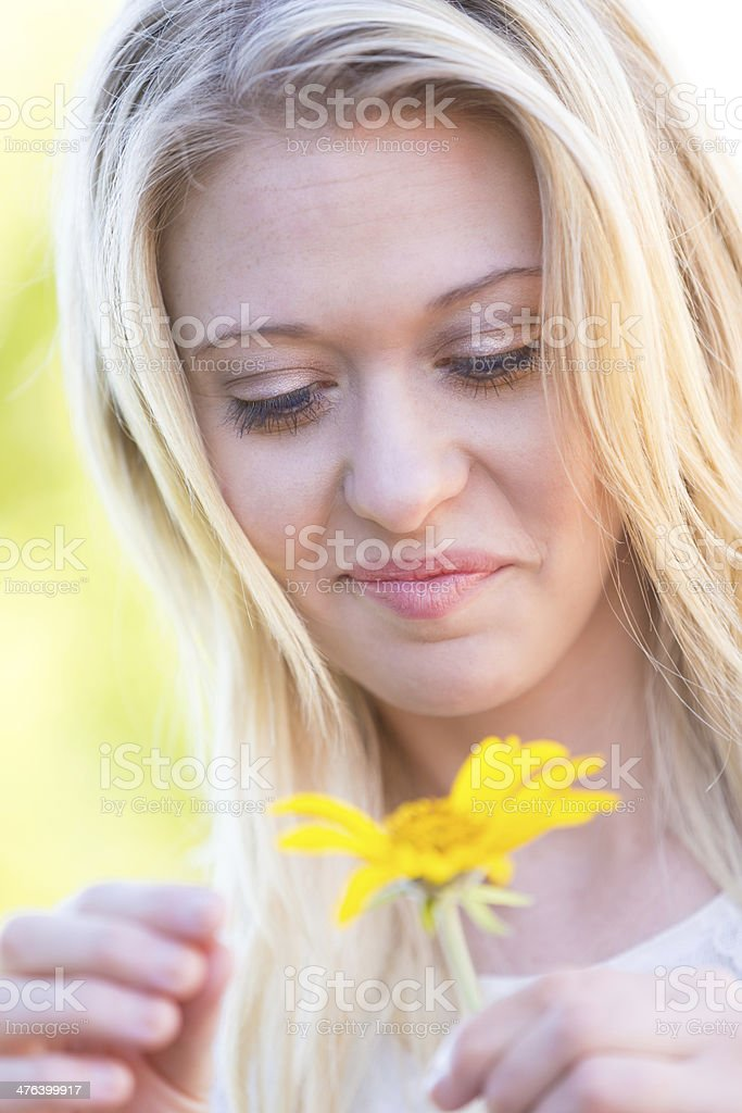 Woman with blonde hair holding yellow daisy stock photo