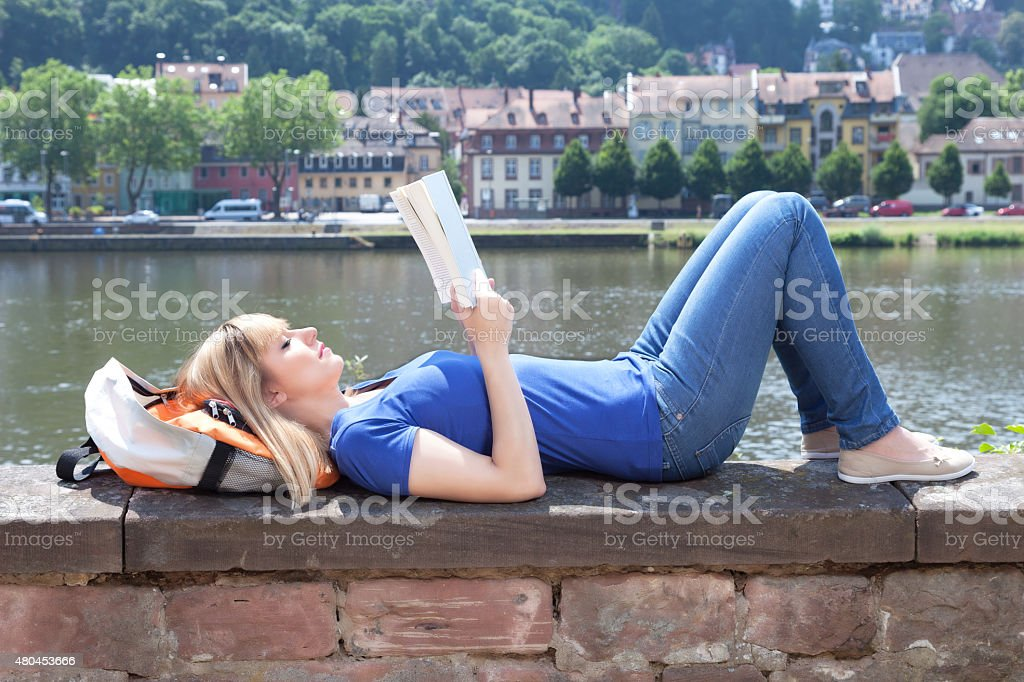 Woman with blonde hair reading a book on a river stock photo