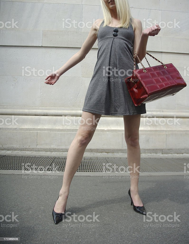 Woman with Blonde Hair Spinning Red Handbag royalty-free stock photo