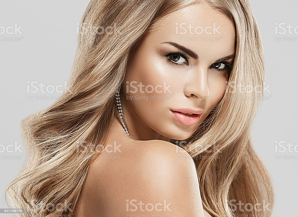 Woman with blonde hair. Studio shot. Gray background. stock photo