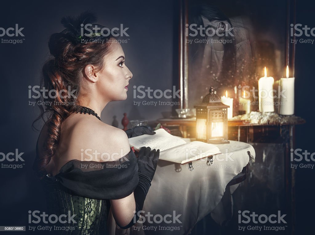 Woman with book and ghost in the mirror stock photo