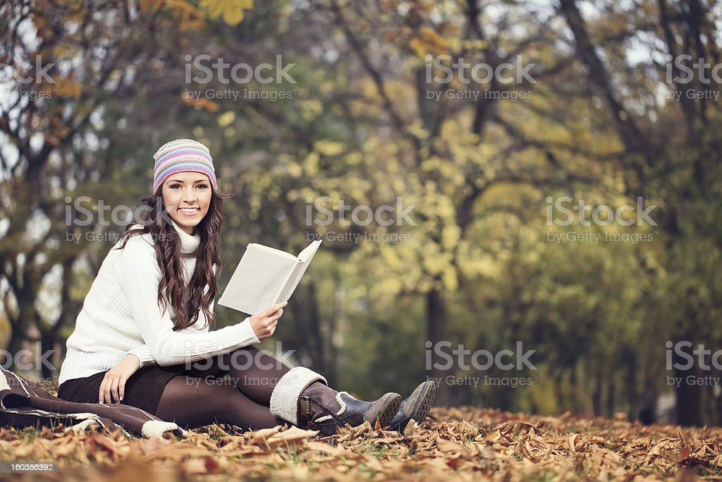 woman with book in autumn park royalty-free stock photo