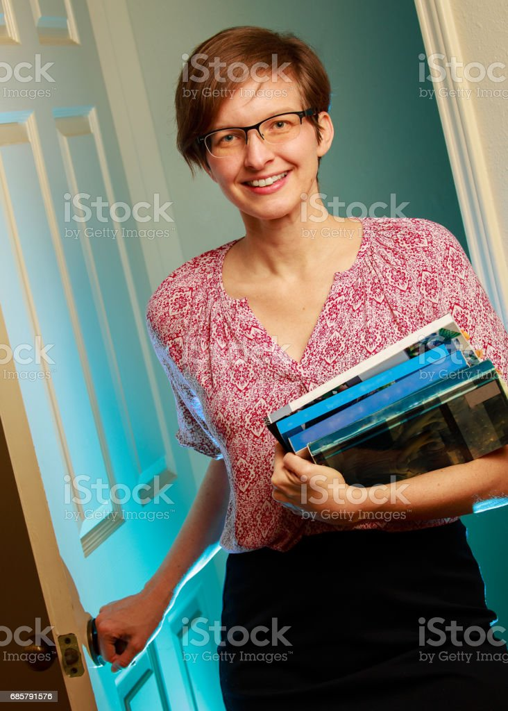 Woman with books entering room stock photo