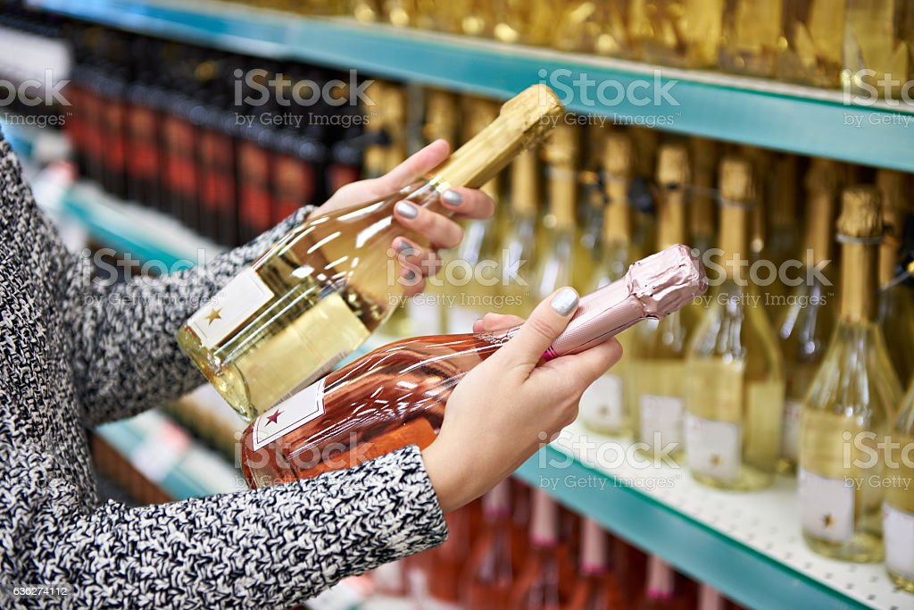Woman with bottles of rose and white wine in store stock photo