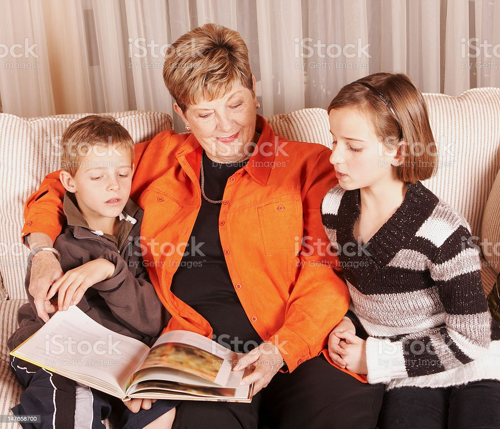 Woman with boy and girl reading royalty-free stock photo