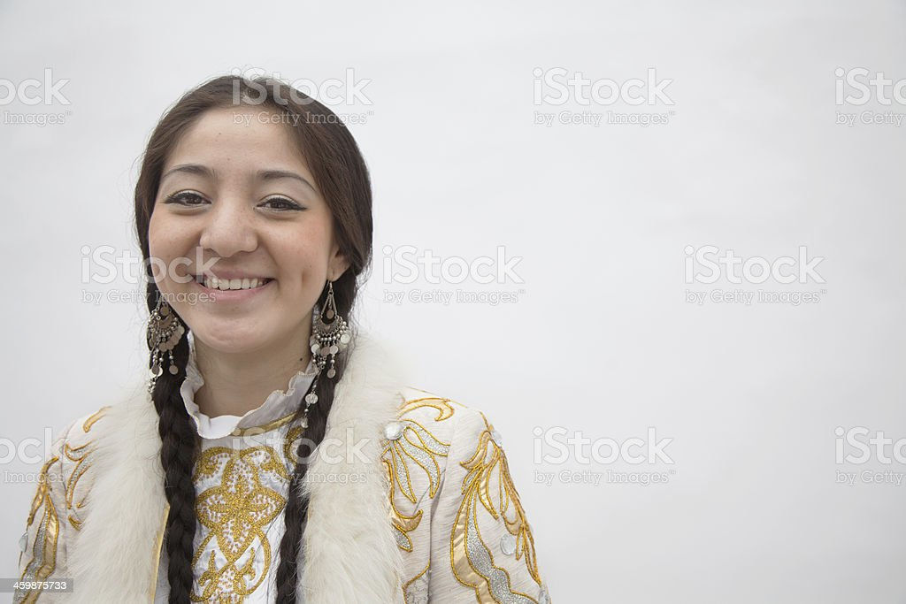 Woman with braids in traditional clothing from Kazakhstan, studio shot stock photo