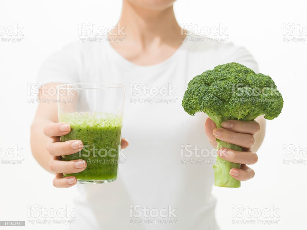 Woman with broccoli and a green smoothie stock photo