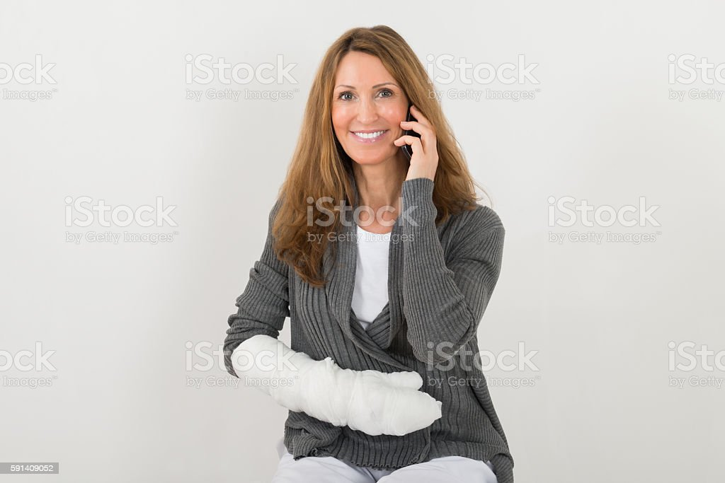 Woman With Broken Hand Talking On Mobile Phone stock photo