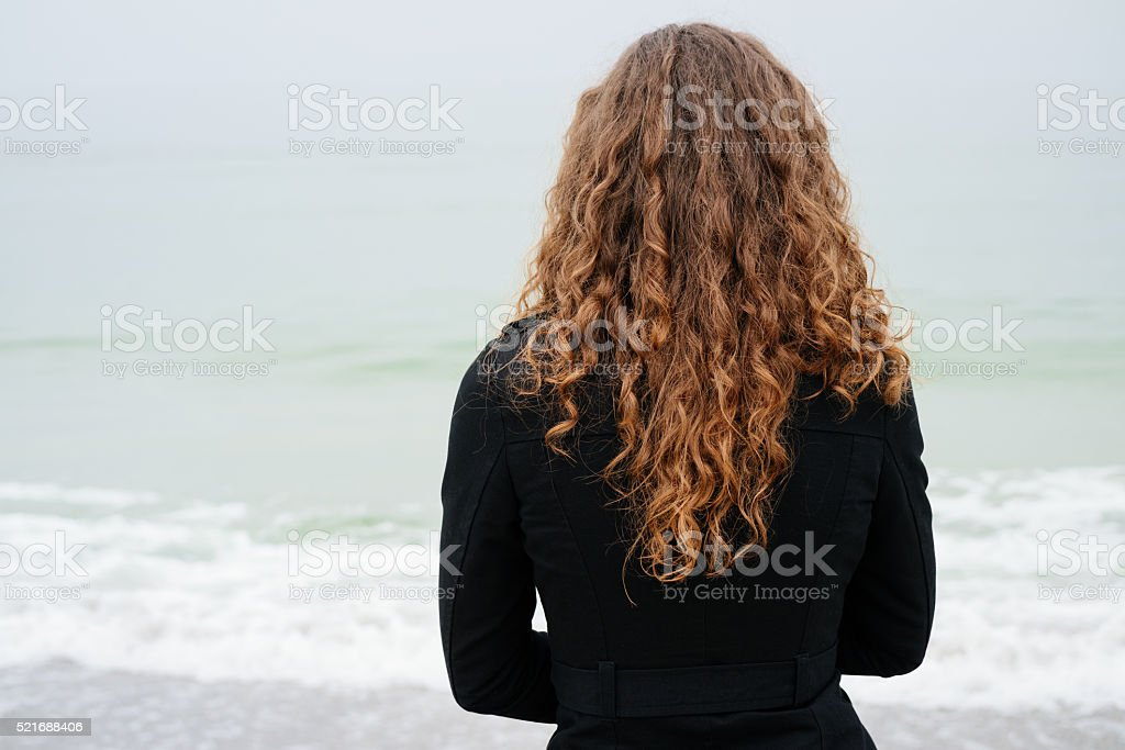 Woman with brown curly hair in a black coat stock photo