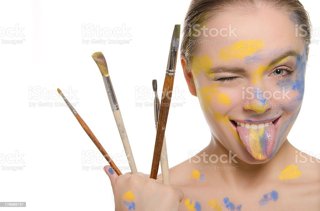 woman with brushes and paint on his face shows tongue royalty-free stock photo