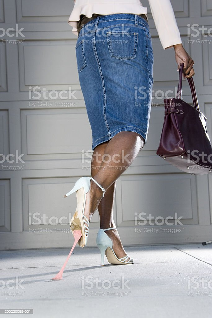 Woman with bubblegum stuck on bottom of shoe, low section, rear view stock photo