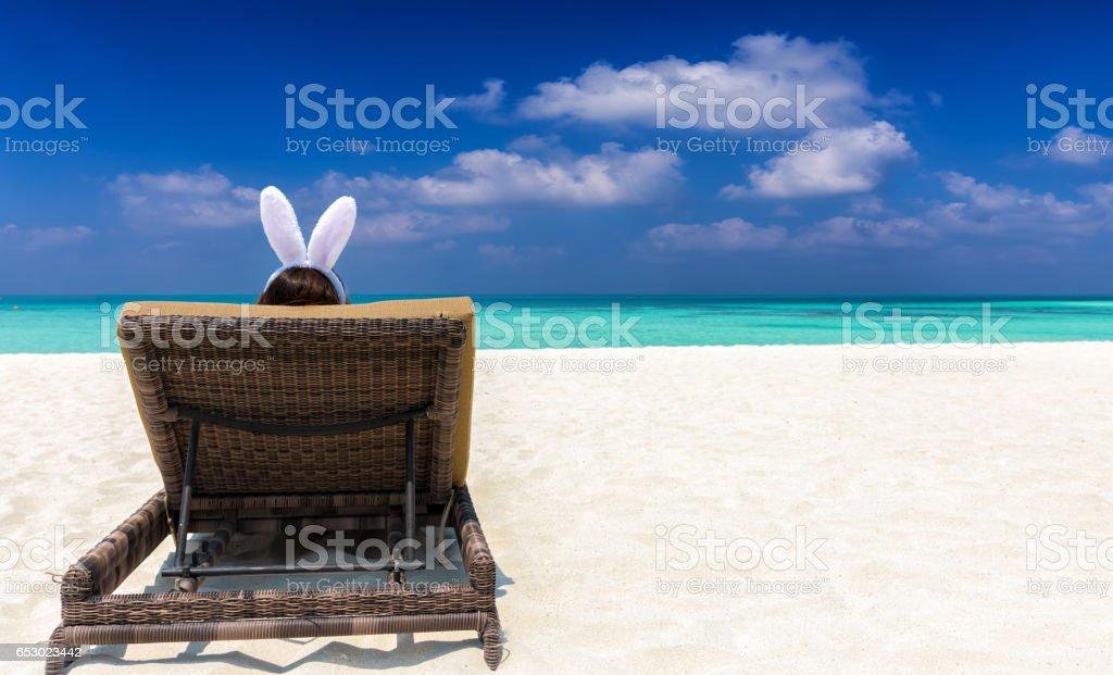 Woman with bunny ears on a sun chair at a tropical beach stock photo