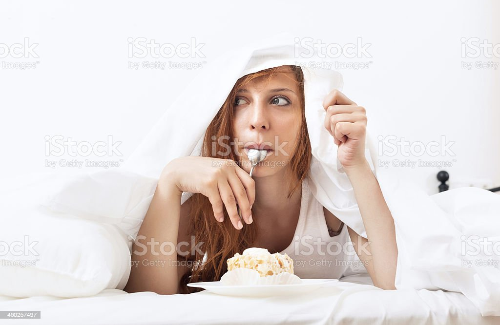 Woman with cake and spoon in bed stock photo