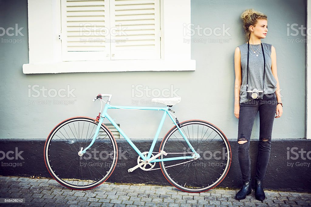Woman with camera standing by bicycle stock photo