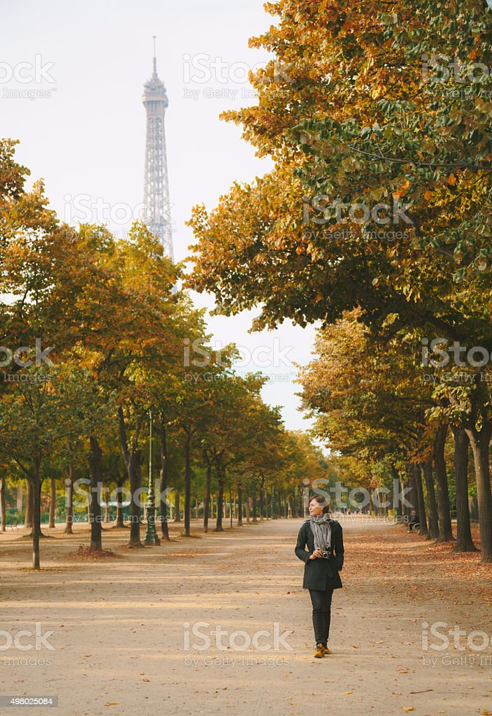 Woman with camera walking in Champ de Mars in Paris. stock photo