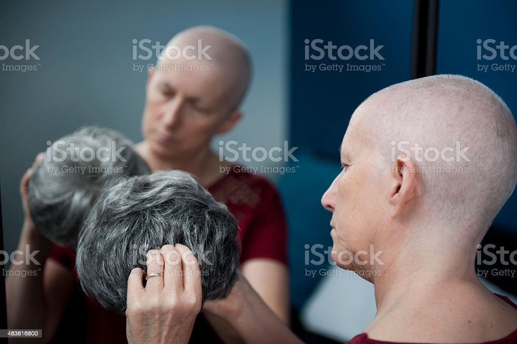 Woman with Cancer about to put on Wig stock photo