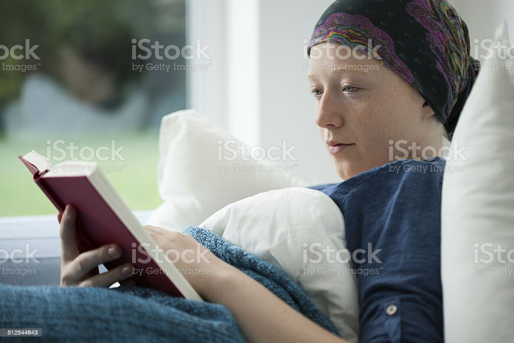 Woman with cancer reading a book stock photo