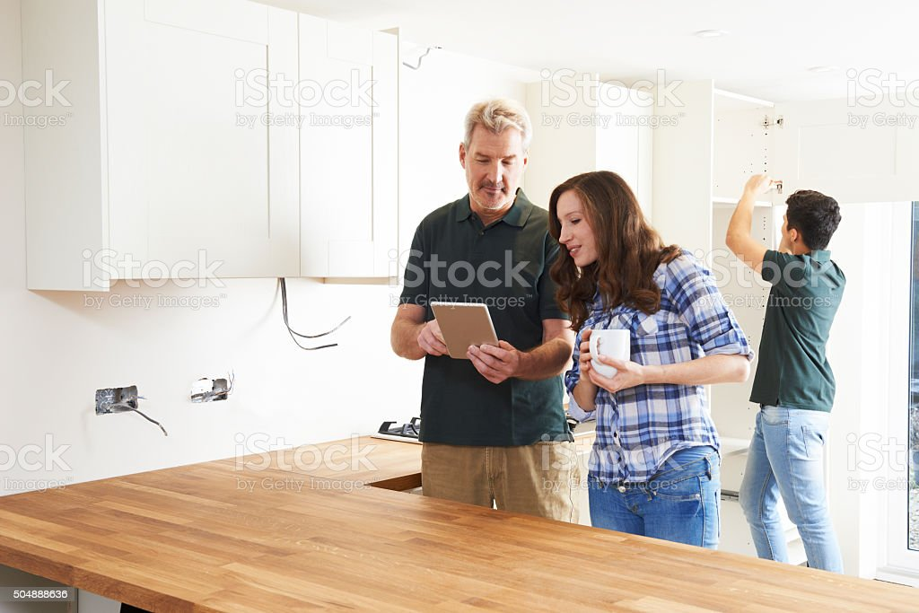 Woman With Carpenter Looking At Plans For Kitchen stock photo