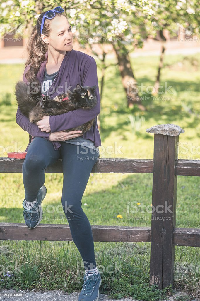 Woman with cat outside sitting on fence stock photo