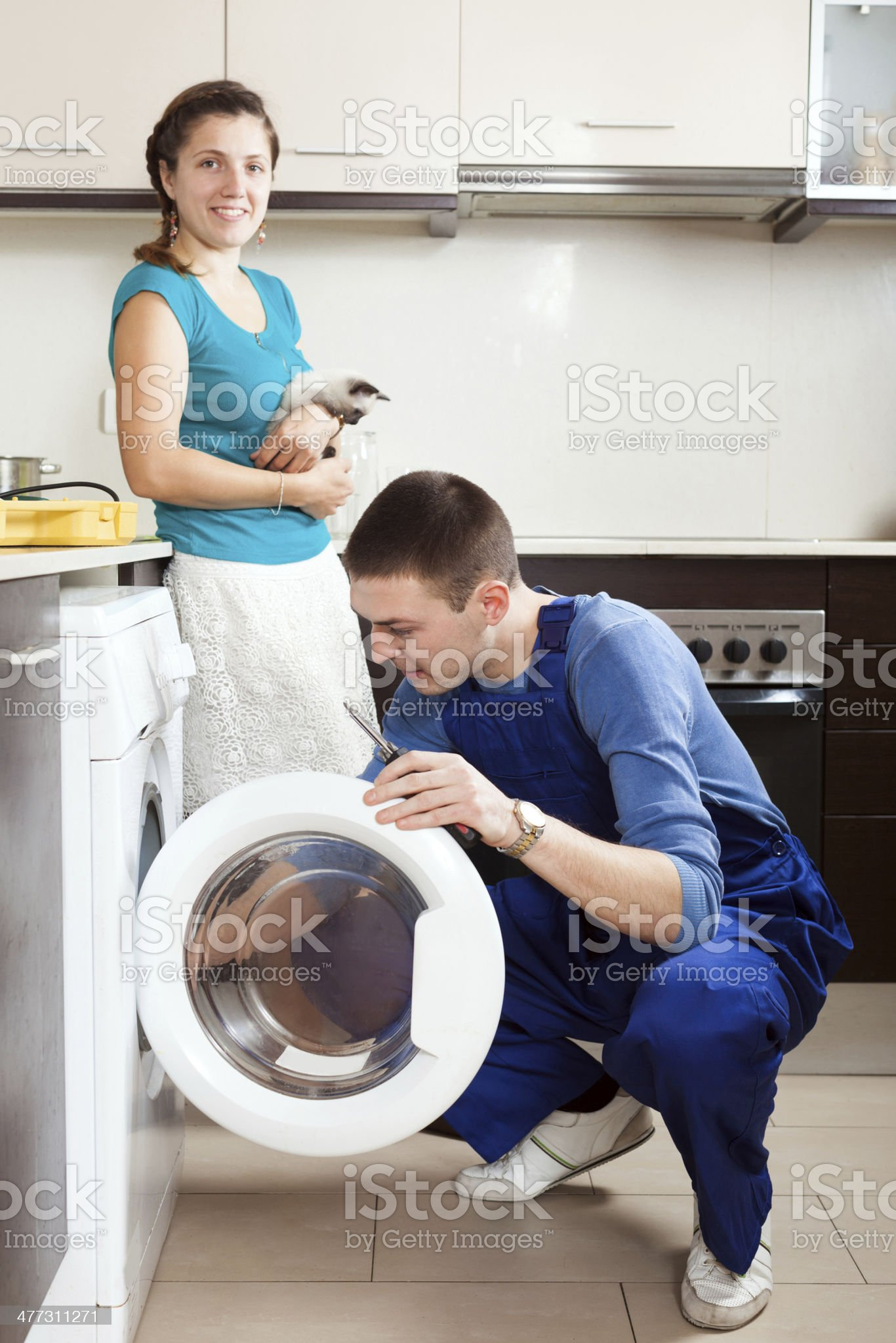 Woman with cat  watching as worker repairing washing machine royalty-free stock photo