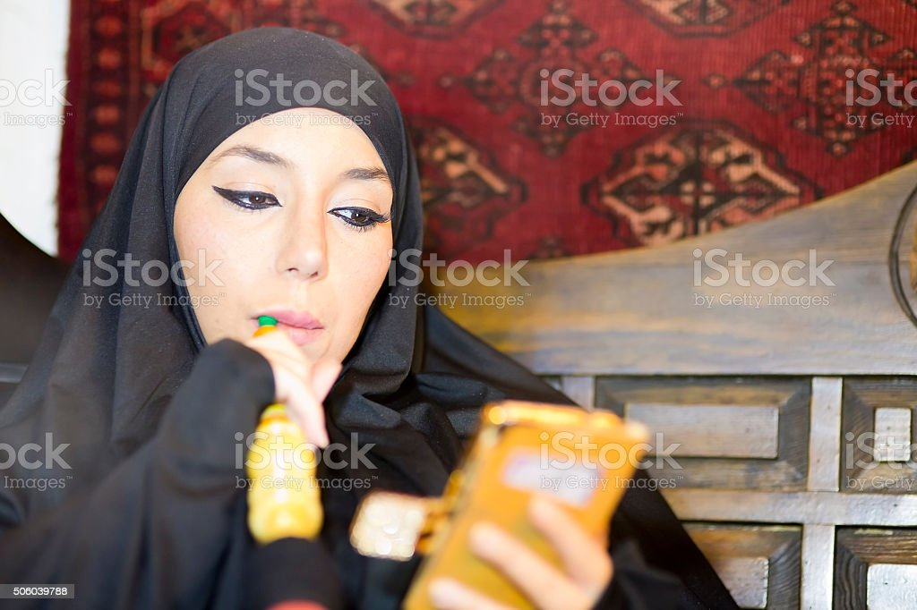 Woman with chador headscarf using mobile phone stock photo