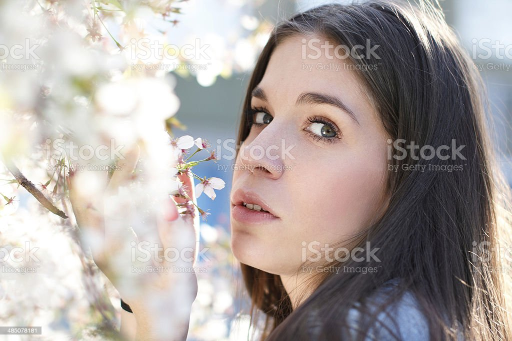Woman with cherry flower look into camera royalty-free stock photo
