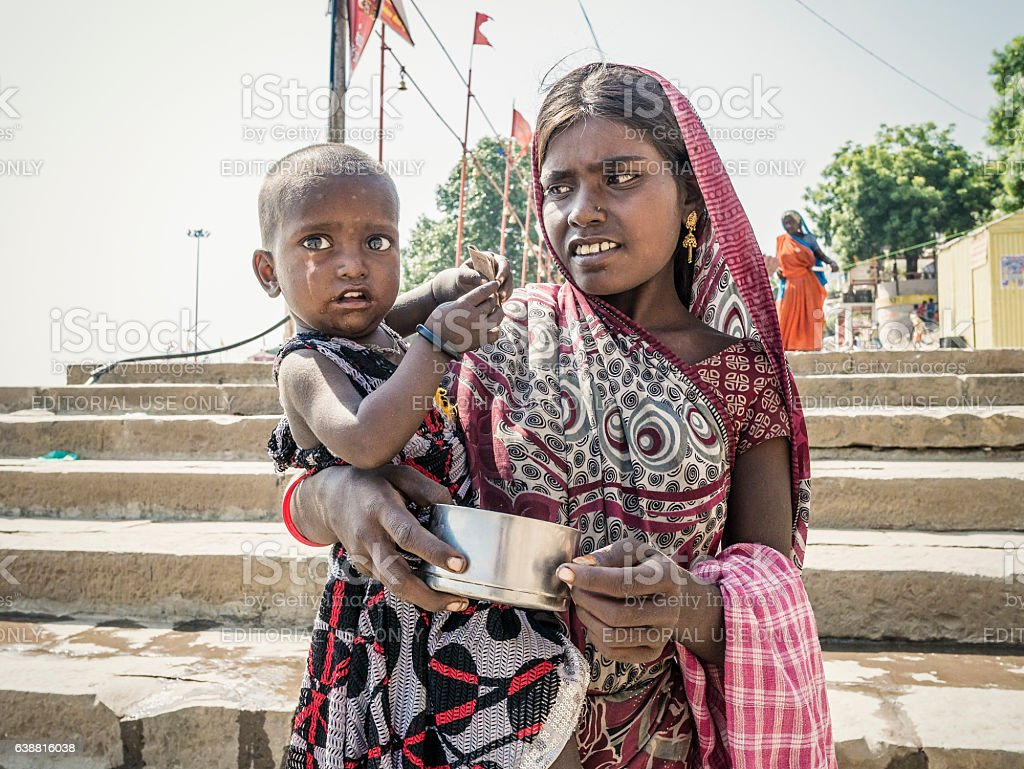 Woman with child begging for money in Varanasi India stock photo