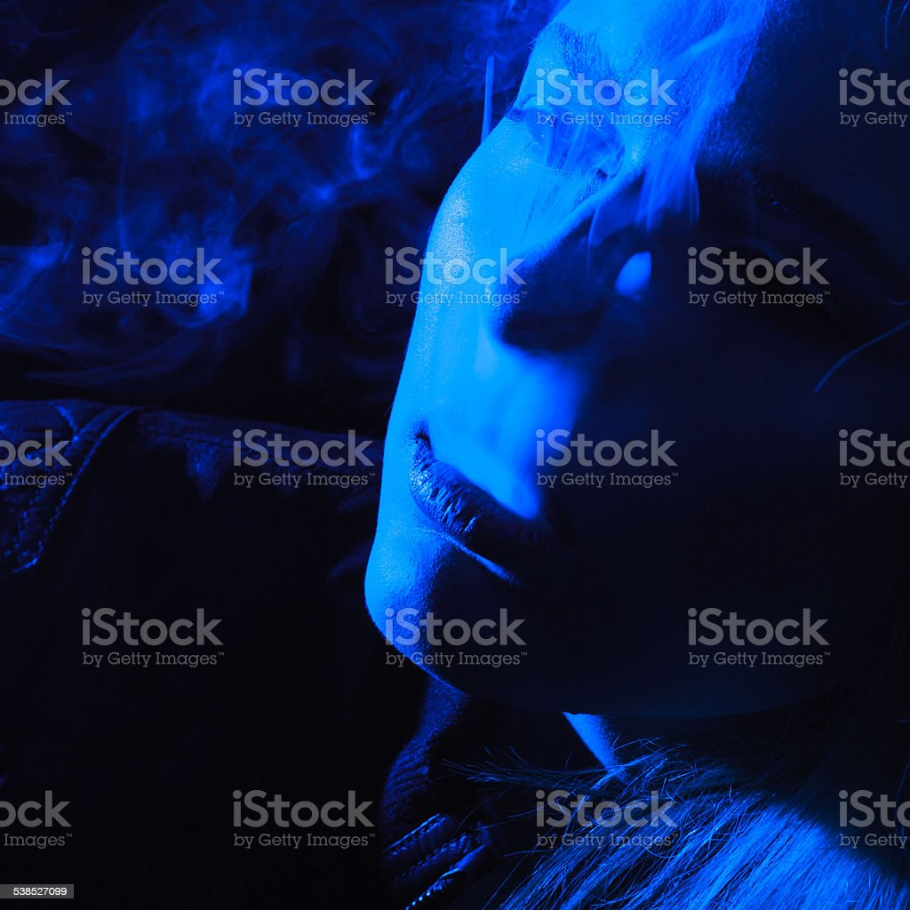 Woman with Cigarette Exhaling Smoke stock photo
