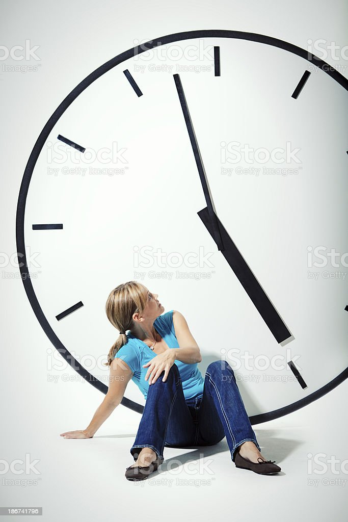 Woman with Clock Worrying about Managing Time stock photo