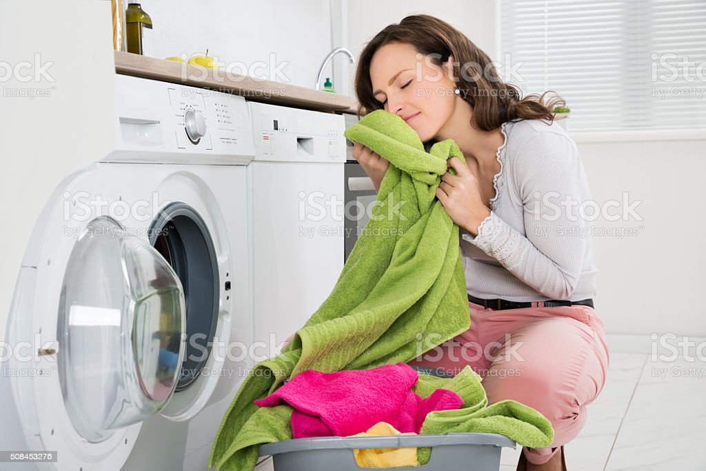 Woman With Clothes Near The Washer stock photo