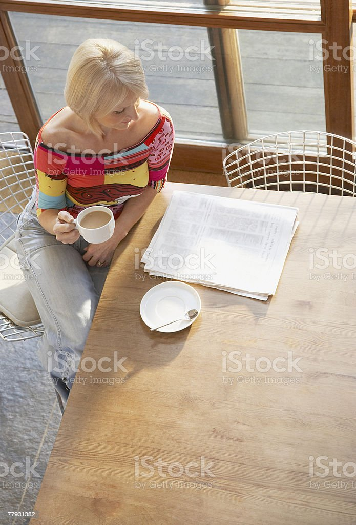 Woman with coffee and a newspaper at kitchen table royalty-free stock photo